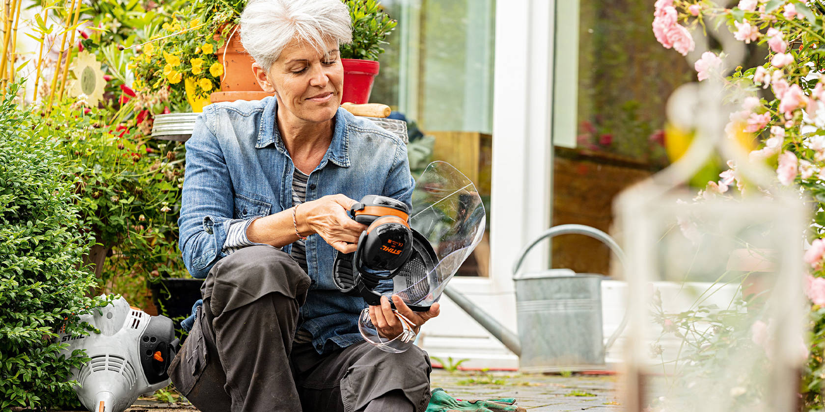 Woman sitting in front of a house with face/hearing protection in her hand, next to her is a STIHL FS 56 R gasoline driven brushcutter
